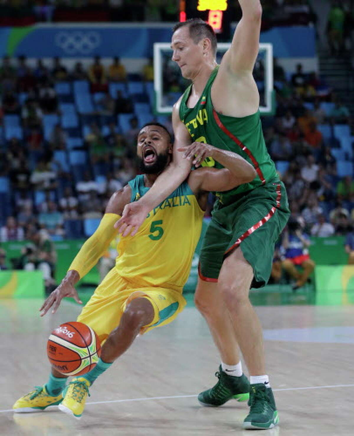 Australia's Patty Mills (5) is fouled by Lithuania's Paulius Jankunas (13) during a men's quarterfinal round basketball game against Australia at the 2016 Summer Olympics in Rio de Janeiro, Brazil, Wednesday, Aug. 17, 2016. (AP Photo/Eric Gay)