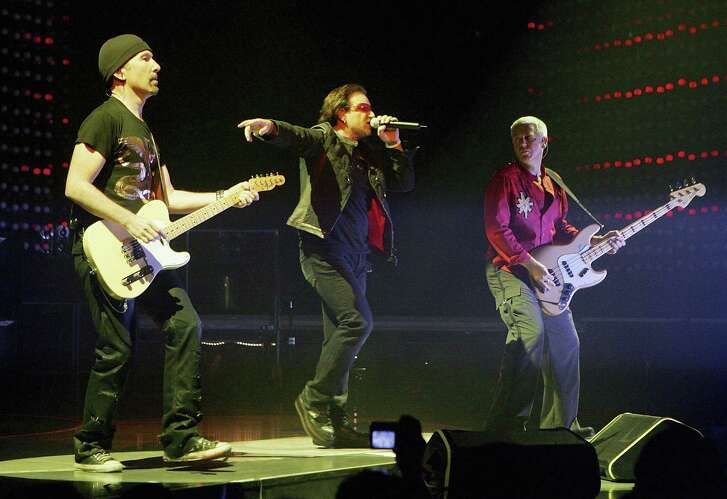 """LAS VEGAS - NOVEMBER 04:  U2 guitarist The Edge (L), singer Bono (C) and bassist Adam Clayton perform during the first of two sold-out shows of their """"Vertigo"""" tour at the MGM Grand Garden Arena November 4, 2005 in Las Vegas, Nevada. The band is touring in support of the album """"How To Dismantle An Atomic Bomb.""""  (Photo by Ethan Miller/Getty Images) *** Local Caption *** Bono;The Edge;Adam Clayton"""