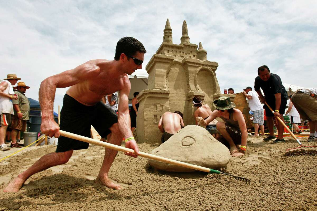 """Carl Stewart (front left) along with other team members work to construct the """"Alice in Wondersand"""" sandcastle during the annual AIA Sandcastle Competition on Galveston's East Beach Saturday, June 5, 2010, in Galveston. ( Michael Paulsen / Houston Chronicle )"""