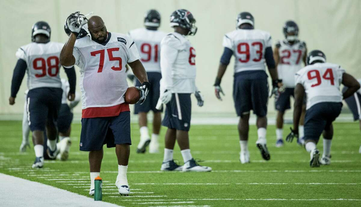 Houston Texans nose tackle Vince Wilfork (75) takes off his helmet as he gets ready to stretch during warm ups at Texans training camp at Houston Methodist Training Center on Wednesday, Aug. 17, 2016, in Houston.