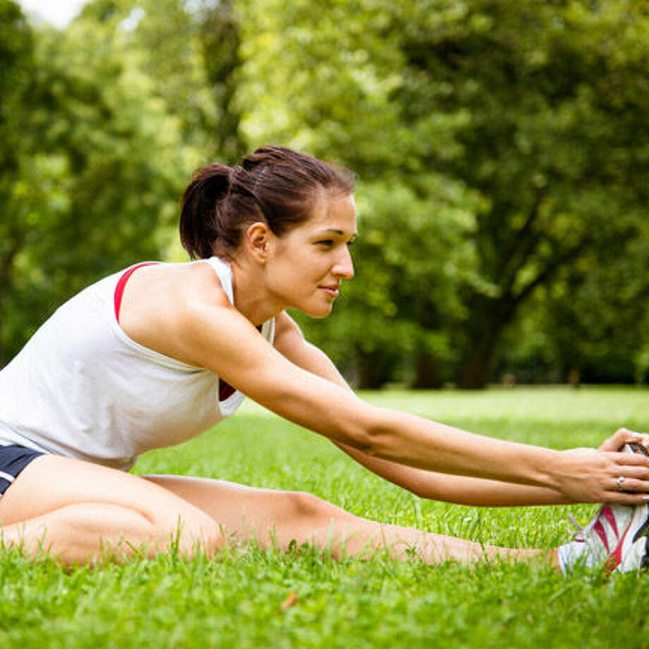 Young fitness woman stretching muscles before sport activity - profile view Photo: Martinan - Fotolia