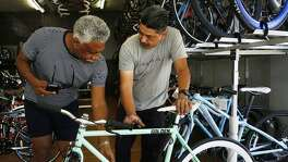 Rikki Williams, a fixed gear bike fan, examines a fixie with employee Juan Reyes at the Just Ride L.A. bike shop. Williams has been riding a fixed gear bike since 2012.