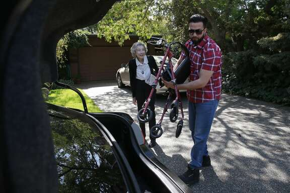 Ursula Moore and UBER car driver Bhawanvir Singh places her walker into the trunk as they get set to leave from her home to keep her appointments in Palo Alto, California, on Wed. Aug. 17, 2016.