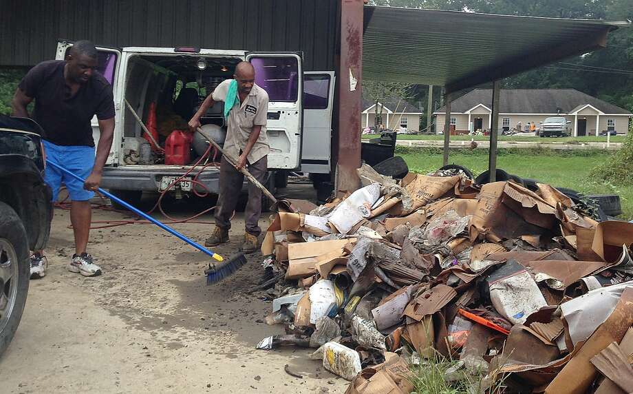 Terry Brewer, left, and Timothy Harris pile up debris outside a flooded auto parts store in Albany, La. on Wednesday, Aug 17, 2016. The U.S. Small Business Administration plans to open several south Louisiana locations to help businesses damaged by record flooding. Louisiana's economic development office is encouraging business owners to register for federal disaster aid and to look at other available support services at www.OpportunityLouisiana.com. (AP Photo/Kevin McGill) Photo: Kevin McGill, Associated Press