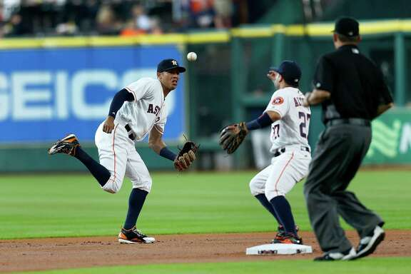 Houston Astros shortstop Carlos Correa (1) picks up the ground ball hit by Stephen Piscotty to throw to Jose Altuve at second base on the double play during the first inning of an MLB game at Minute Maid Park,Wednesday, Aug. 17, 2016, in Houston.