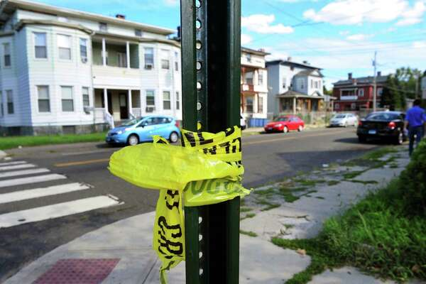 Police tape still clings to a sing post after the shooting death on Tuesday night of Frederick Richardson Jr. on Noble Street in Bridgeport, Conn., on Wednesday Aug. 17, 2016.