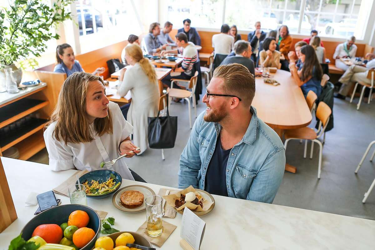 Emily Rudisill (left) and Jared Levan (right) sit at the bar as they eat lunch at Tartine Manufactory in San Francisco, California, on Wednesday, Aug. 17, 2016.