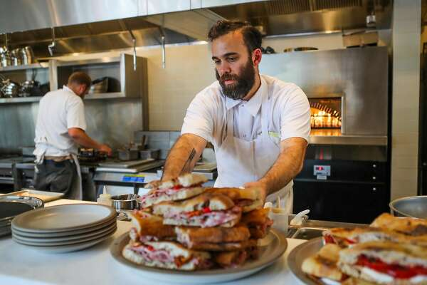 Su chef Bill Niles sets down a plate of sandwiches during the lunch rush at Tartine Manufactory in San Francisco, California, on Wednesday, Aug. 17, 2016.