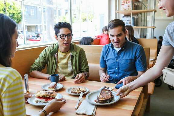 Stephanie Saffouri (left), Elijah Ball (center) and Thomas Dude (right) are served their lunch at Tartine Manufactory in San Francisco, California, on Wednesday, Aug. 17, 2016.