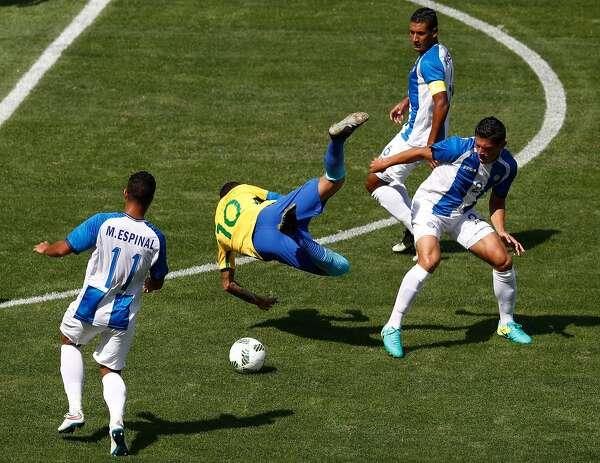 TOPSHOT - Brazil s Neymar (C) is fouled by Honduras  Jhonathan Paz (R) during  their Rio 2016 Olympic Games men s football semifinal match at the Maracana  ... ec8ce00aefbbd