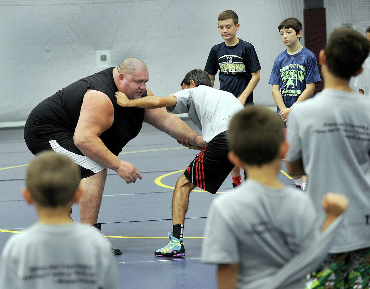 Rulon Gardner, a U.S. Olympic wrestler who won a gold medal in 2000, demonstrates technique with Curtis Urbina, coach for the Newtown Youth Wrestling Assoc. Wednesday, August 17, 2016. Gardner worked with kids at the Newtown Youth Wrestling summer camp at the Newtown Youth Academy Wednesday.