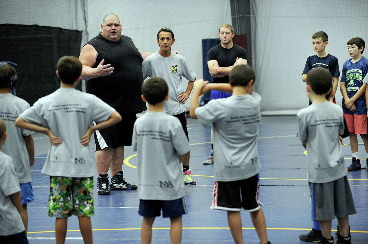 Rulon Gardner, a U.S. Olympic wrestler who won a gold medal in 2000, works with kids at the Newtown Youth Wrestling summer camp at the Newtown Youth Academy Wednesday, August 17, 2016.