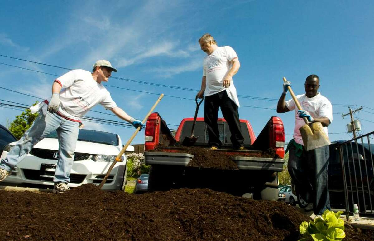 Employees from the Affinion Group, including Ed Vanchot, Mike Romaniw and George Nixon, work on the lawn as they volunteer at the Yerwood Center as part of the 23rd Annual HomeFront Day in Stamford, Conn. on Friday April 30, 2010.