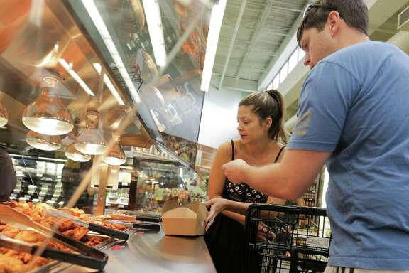 Isabel Gomes and Andrew Atherton go through the wing bar at the Randalls store in Midtown on Wednesday.