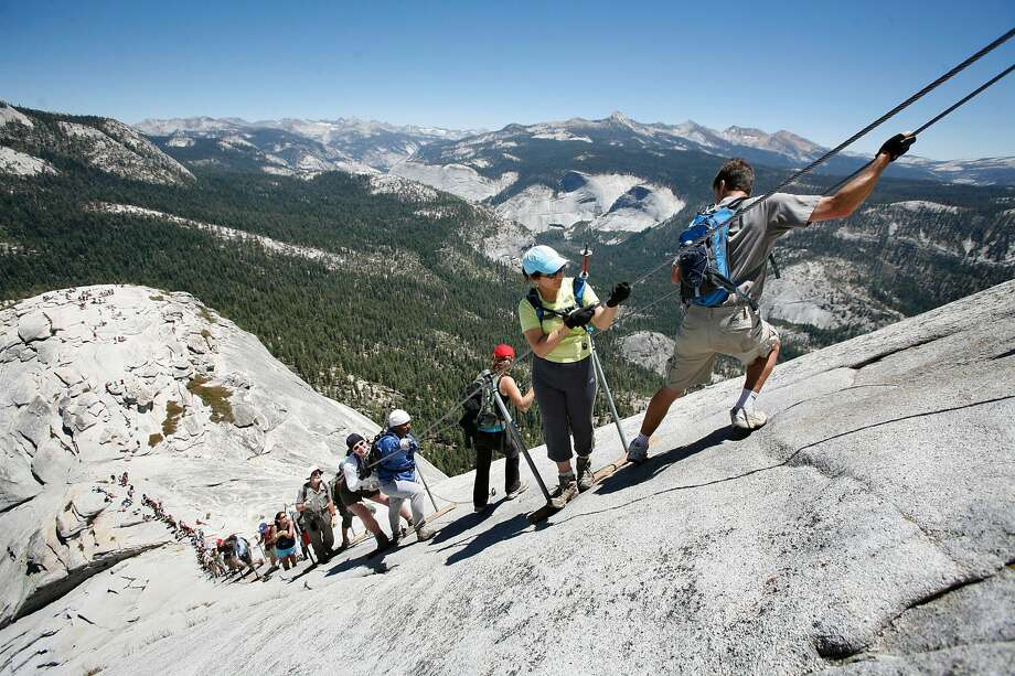 Climbers negotiate the steep pitch of the cable section of half Dome.  The weekend summer crowds climbing Half Dome in Yosemite National Park have raised safety concerns among the climbers and park. Hundreds climb the precarious cable section every summer weekend day - many who are not prepared for the strenuous hike and 100 yard cable climb. Photos taken at Half Dome on Saturday, June 30, 2007.  Photo by Michael Maloney / San Francisco Chronicle Photo: Michael Maloney / The Chronicle