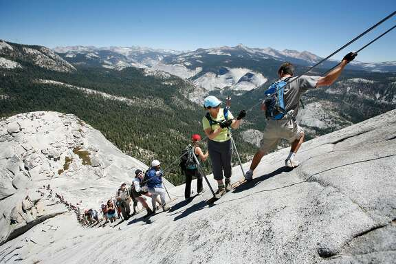 Climbers negotiate the steep pitch of the cable section of half Dome.  The weekend summer crowds climbing Half Dome in Yosemite National Park have raised safety concerns among the climbers and park. Hundreds climb the precarious cable section every summer weekend day - many who are not prepared for the strenuous hike and 100 yard cable climb. Photos taken at Half Dome on Saturday, June 30, 2007.  Photo by Michael Maloney / San Francisco Chronicle