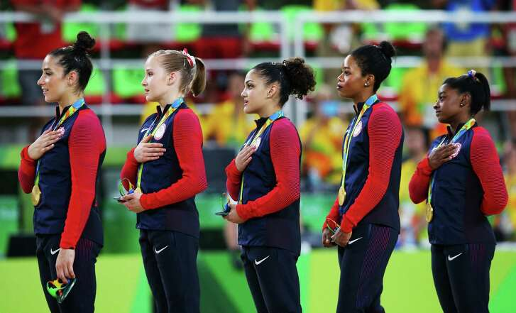 Simone Biles, Gabrielle Douglas, Lauren Hernandez, Madison Kocian and Alexandra Raisman of the United States listen to the national anthem on the Olympic podium. (Getty Images)