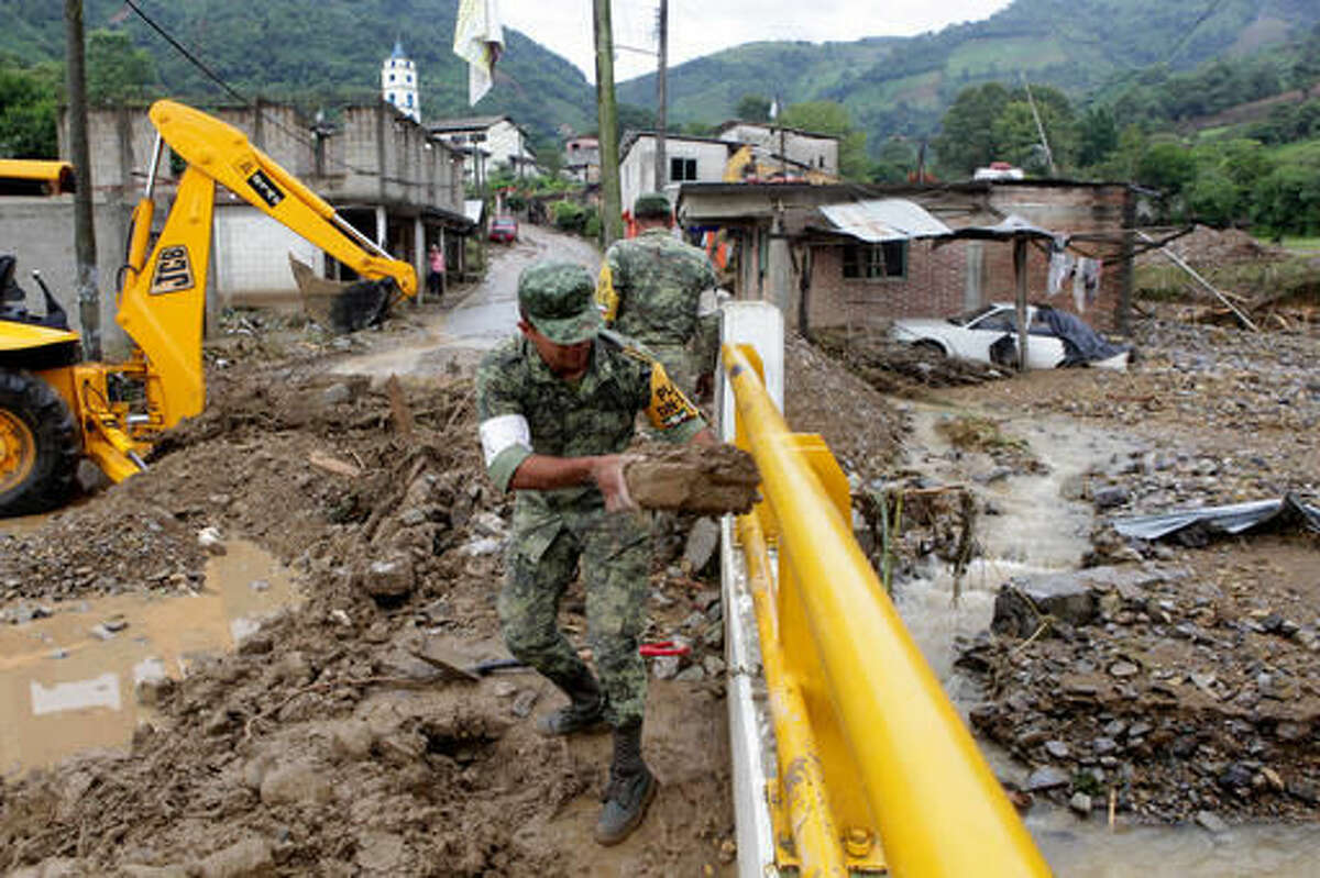 Mexican soldiers remove mud and debris off a bridge damaged by a mudslide in Xaltepec, Mexico, Monday, Aug. 8, 2016. Mountain communities in two Mexican states are recovering from weekend mudslides that killed dozens during heavy rains brought by remnants of Hurricane Earl. (AP Photo/Pablo Spencer)