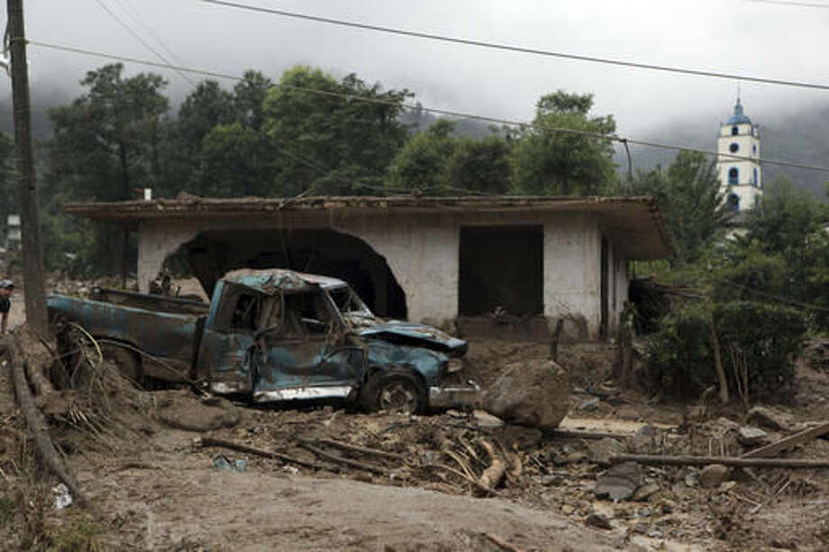 A pickup truck lays destroyed next to a house damaged by a mudslide in Xaltepec, on the mountainous north of Puebla state, Mexico, Sunday, Aug. 7, 2016. The death toll from the remnants of Hurricane Earl grows to more than 30 in Mexico as a new tropical storm forms off the country's Pacific Coast. (AP Photo/Pablo Spencer) Photo: Pablo Spencer