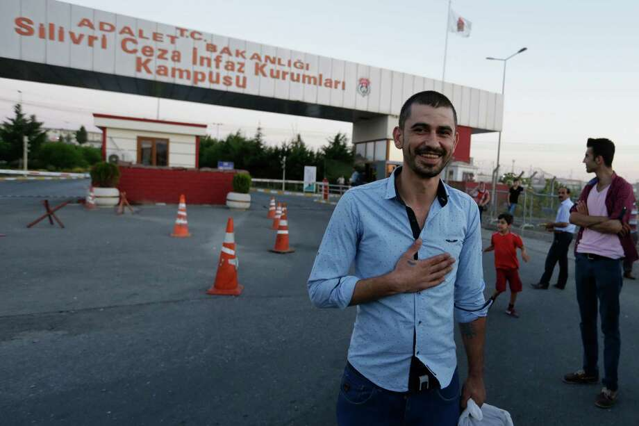 Emrah Pasa Alissoy, 27, thanks media after he was released from a high security prison complex in Silivri, about 80 kilometers (50 miles) west of Istanbul, Wednesday, Aug. 17, 2016. Turkey issued a decree Wednesday paving the way for the conditional release of some 38,000 prisoners, the justice minister said, an apparent move to reduce its prison population to make space for thousands of people who have been arrested as part of an investigation into last month's failed coup. (AP Photo/Thanassis Stavrakis) ORG XMIT: XTS110 Photo: Thanassis Stavrakis / Copyright 2016 The Associated Press. All rights reserved. This m