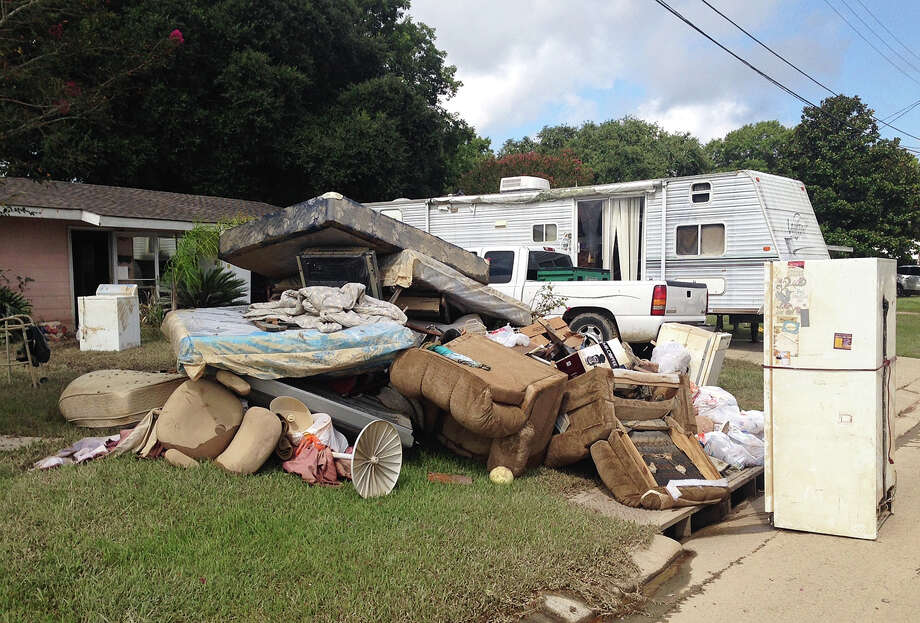 A growing pile of debris sits outside the flood-ravaged home of Carolyn and James Smith in Denham Springs, La. on Wednesday, Aug 17, 2016. Smith says she and four other adults will live for the time being in the travel trailer that one of her sons towed to the driveway after weekend flooding inundated the area. (AP Photo/Kevin McGill) ORG XMIT: LAKM102 Photo: Kevin McGill / Copyright 2016 The Associated Press. All rights reserved. This m