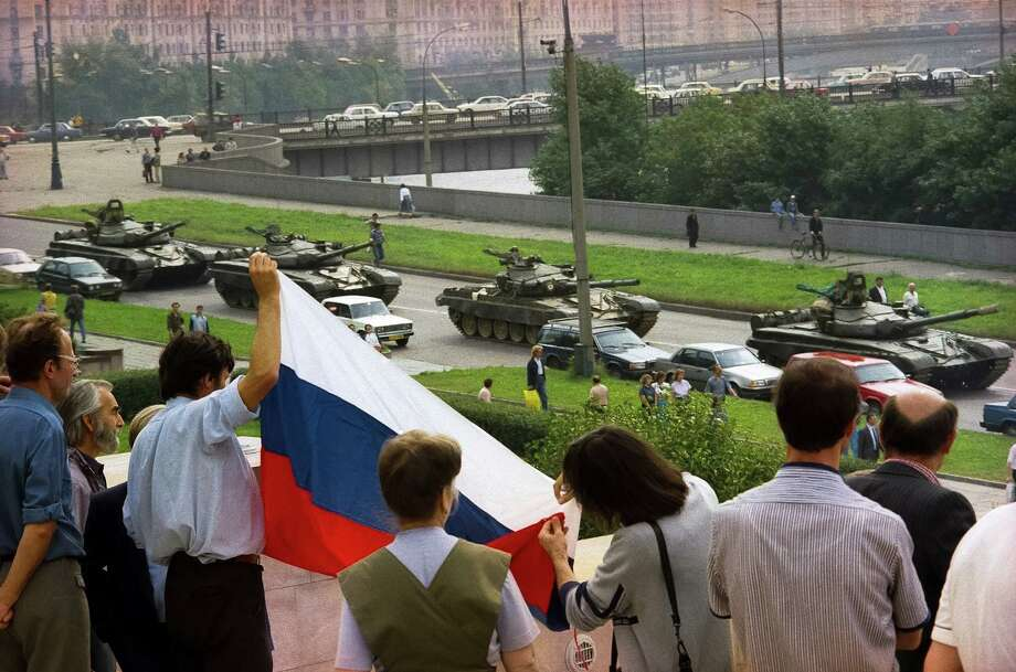 FILE - In this Aug. 19, 1991 file photo, protesters gather at the Russian Government building, also known as White House, holding a Russian national flag as they protest the oncoming line of tanks around the building in Moscow, Russia. As the 25th anniversary of the so-called August Coup draws near this Friday, The Associated Press has talked to participants and witnesses of those critical days when Muscovites turned out to defend the spirit of democracy that Gorbachev had unleashed, and many Soviet officers defied their orders and sided with the people, ensuring that that the plotters failed. (AP Photo/Alexander Zemlianichenko, file) ORG XMIT: XAZ501 Photo: Alexander Zemlianichenko / Copyright 2016 The Associated Press. All rights reserved. This m