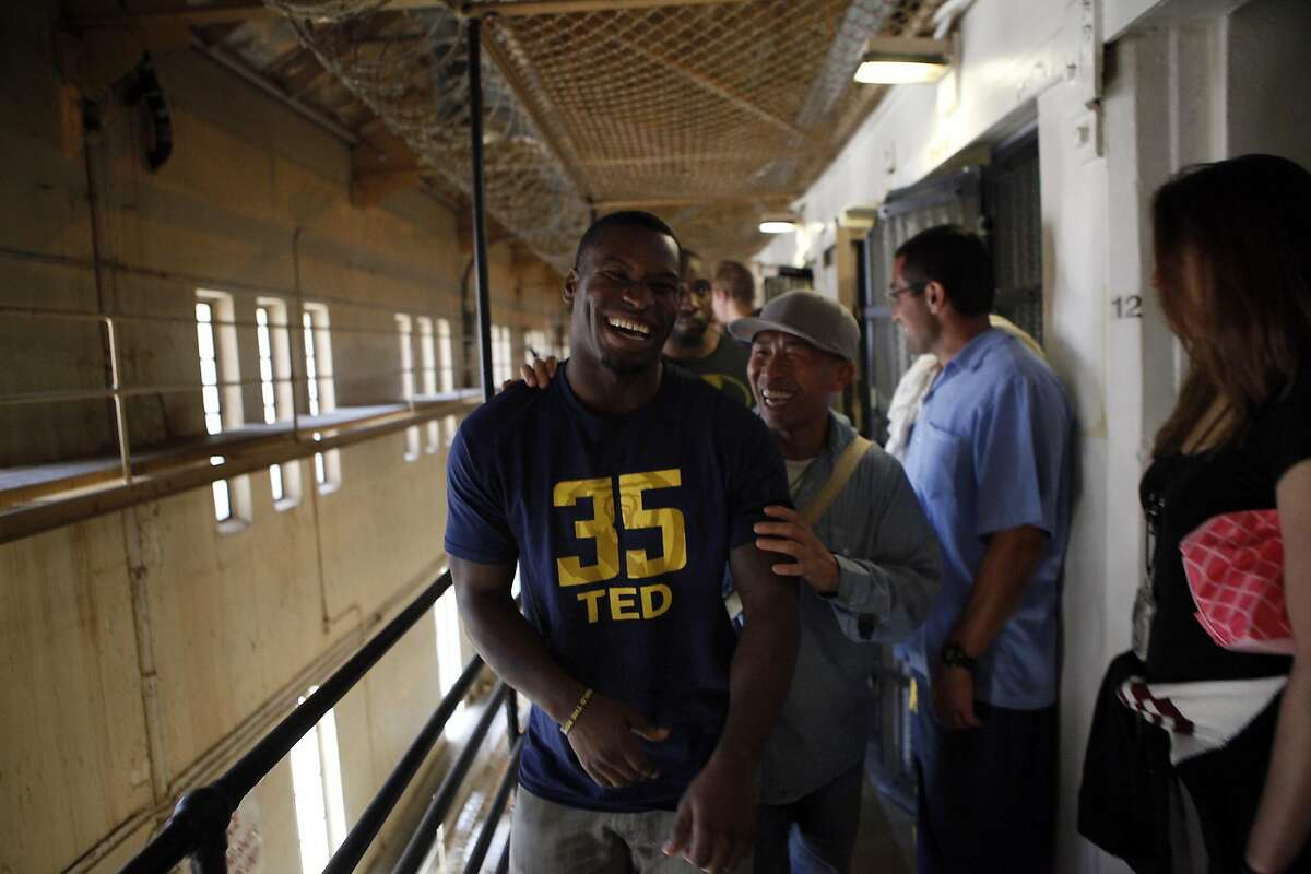 Safety Damariay Drew laughs with an inmate inside a housing block as Cal Bears football players make a visit to San Quentin State Prison in San Quentin, CA, Saturday May 3, 2014.