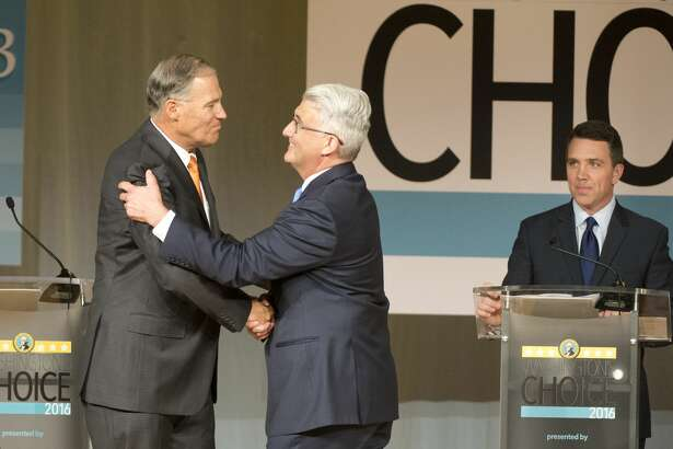 Washington Gov. Jay Inslee, left, shakes hands with challenger Bill Bryant before the two debate at Spokane Falls Community College, Wednesday, Aug. 17, 2016, in Spokane, Wash. Moderator Sean Owsley of KHQ-TV stands at right. (Jesse Tinsley/The Spokesman-Review via AP)