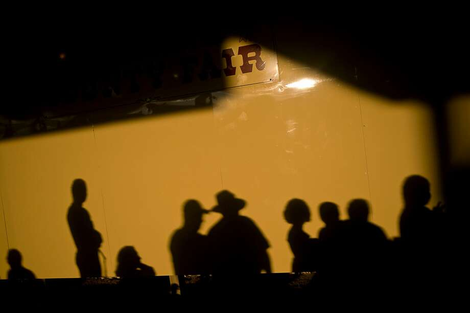 Auction attendees cast shadows while waiting to sell animals at the Small Animal Auction on Wednesday. Photo: Erin Kirkland/Midland Daily News/Erin Kirklamd