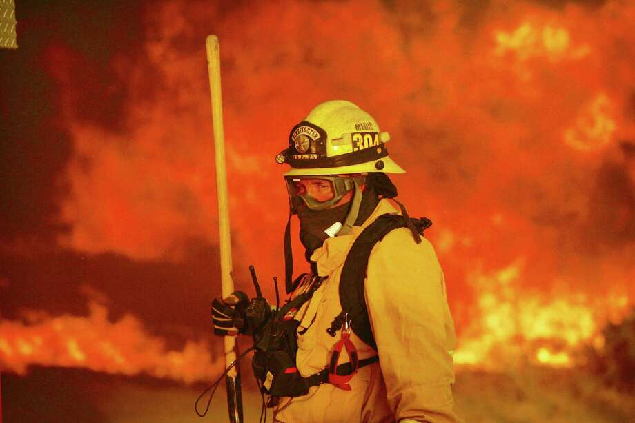 A firefighter prepares to battle a wildfire in the Cajon Pass in San Bernardino county, Calif., on Tuesday, Aug. 16, 2016. The wildfire that began as a small midmorning patch of flame next to Interstate 15 in the Cajon Pass had by Tuesday's end turned into a 28-square-mile monster that burned an untold number of homes.  (Stan Lim /The Press-Enterprise via AP) ORG XMIT: CARIE202 Photo: Stan Lim / The Press-Enterprise