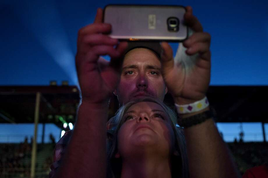 Gary Lucas of Morehead, KY, left, and  Bella Brimm of Harrison watch Chase Rice perform at the Midland County Fair Grandstands Wednesday evening. Photo: Brittney Lohmiller/Midland Daily News/Brittney Lohmiller