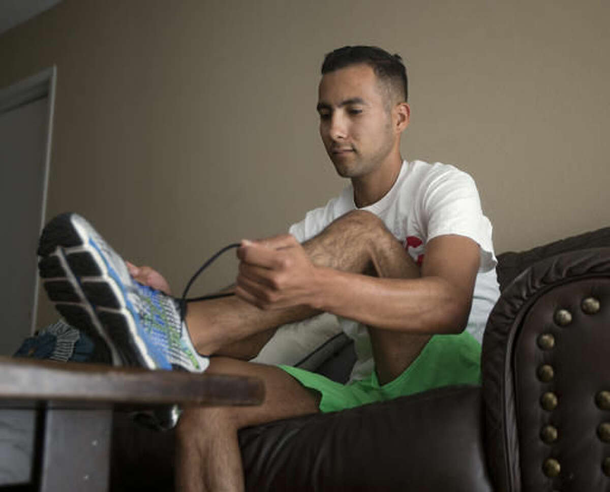 ADDS BACKGROUND INFO ON VILLARREAL - FILE - In this file photo taken July 21, 2016, Anthony Villarreal ties his running shoe at his home in Citrus Heights, Calif. Villarreal, 25, a former track and cross country athlete at William Jessup, is among those who say they would have benefited if the law were in place. He says the university dismissed him in 2013 after learning that he lived with his boyfriend.Democratic California lawmaker Sen. Ricardo Lara, of Bell Gardens, Calif., is removing a contentious provision of his bill that would have allowed LGBT students to more easily sue religious schools for discrimination, Wednesday, Aug. 10, 2016. (AP Photo/Rich Pedroncelli, File)