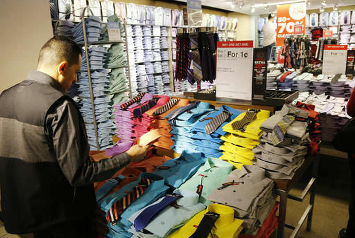 """In this Thursday, March 10, 2016, photo, a man looks at shirts and neckties that are part of a """"Buy One Get One for a Penny"""" sale at a J.C. Penney store. J.C. Penney, Nordstrom, Macy's and Kohl's are reinventing themselves amid stiffer competition from online and discount stores like T.J. Maxx. The changes are the most dramatic in the department stores' storied history. Penney now says it will be less reliant on clothing. (AP Photo/Mark Lennihan)"""