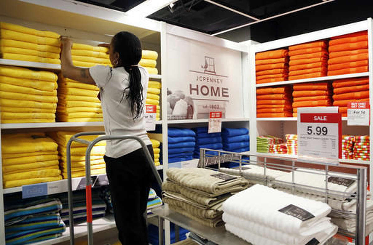 """In this Thursday, March 10, 2016, photo, a sales clerk arranges towels that are part of a """"Buy One Get One for a Penny"""" sale at a J.C. Penney store, in New York. J.C. Penney, Nordstrom, Macy's and Kohl's are reinventing themselves amid stiffer competition from online and discount stores like T.J. Maxx. The changes are the most dramatic in the department stores' storied history. Penney now says it will be less reliant on clothing. (AP Photo/Mark Lennihan)"""