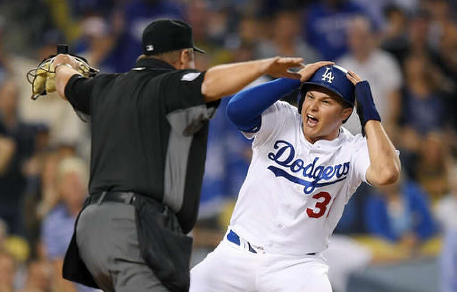 Los Angeles Dodgers' Joc Pederson, right, reacts after being called safe by home plate umpire Marvin Hudson, scoring on a single by Howie Kendrick during the second inning of a baseball game against the Pittsburgh Pirates, Friday, Aug. 12, 2016, in Los Angeles. (AP Photo/Mark J. Terrill) Photo: Mark J. Terrill