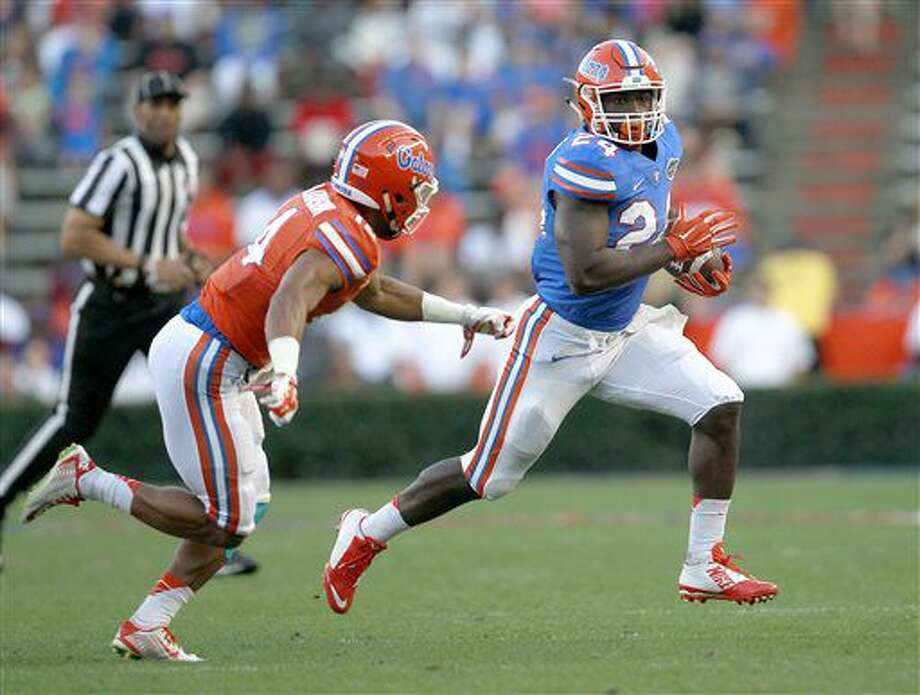 FILE - In this April 8, 2016, file photo, Florida running back Mark Thompson runs upfield past defensive back Chris Williamson during a spring NCAA college football game in Gainesville, Fla. The junior college transfer wants to have 1,000 yards rushing through seven games. That's fairly high-reaching, especially for someone who isn't the starter, has never played a down in the Southeastern Conference and has plenty of competition for carries. (Matt Stamey,/The Gainesville Sun via AP, File) Photo: Matt Stamey