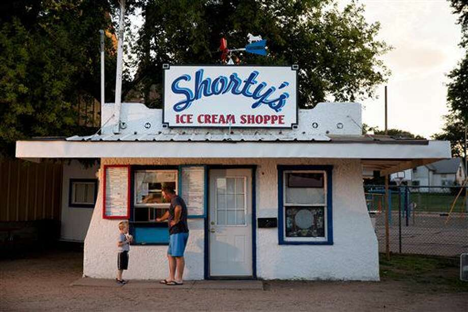 This photo taken July 21, 2016, shows Matt Pelster and his son Liam ordering ice cream from Shorty's in Albion, Neb. Shorty's serves up guilty pleasure. But this tiny snack shack in a town two hours northwest of Omaha also is offering something else: the past. (Ryan Soderlin/The World-Herald via AP) Photo: Ryan Soderlin