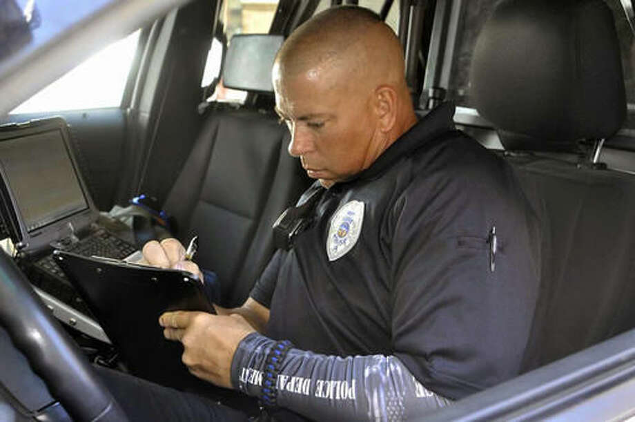 ADVANCE FOR WEEKEND EDITIONS AUG. 13-14 - In this Aug. 5, 2016 photo, Fort Dodge Police Officer Paul Samuelson fills out a report in his patrol car in Fort Dodge, Iowa. During the day, Fort Dodge Police Officer Paul Samuelson patrols the streets of Fort Dodge helping to keep the citizens of the community safe. But at night, Samuelson works at his other job as a police dog trainer. (Peter Kaspari/The Messenger via AP) MANDATORY CREDIT Photo: Peter Kaspari