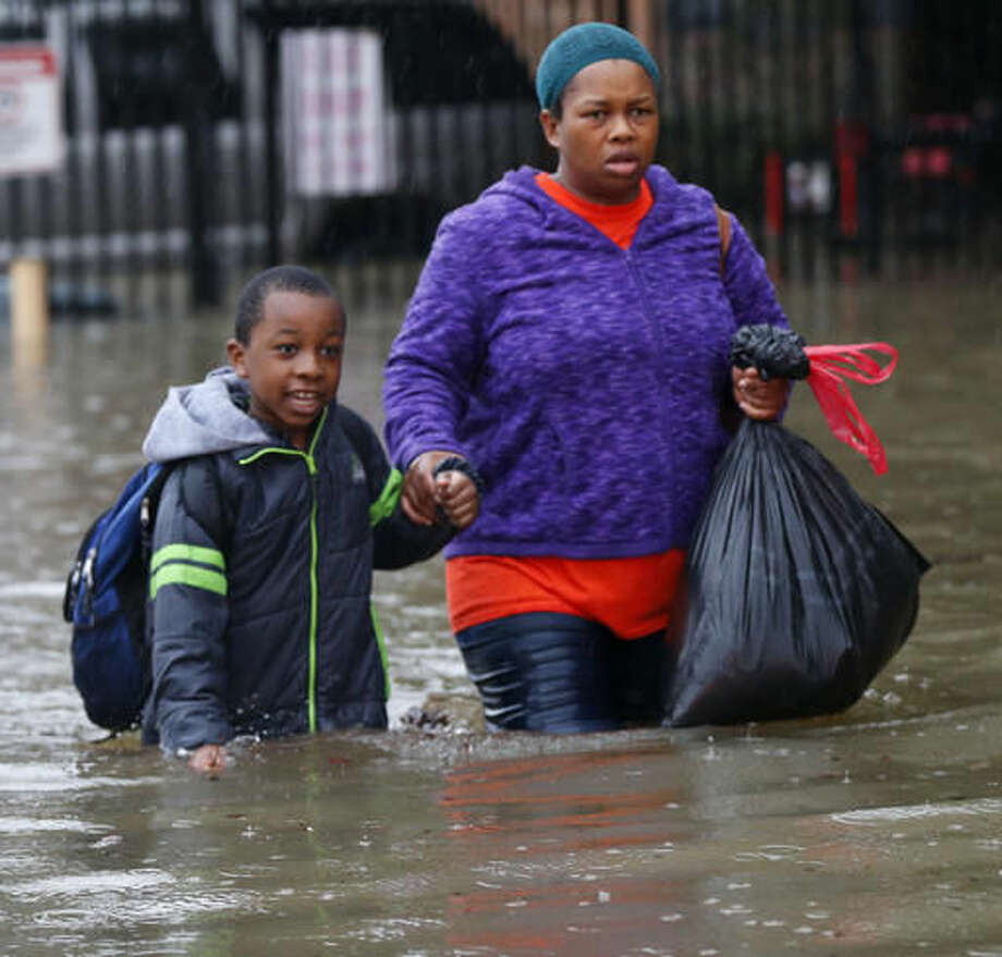 Residents wade through floodwaters from heavy rains in the Chateau Wein Apartments in Baton Rouge, La., Friday, Aug. 12, 2016. Heavy downpours pounded parts of the central U.S. Gulf Coast on Friday, forcing the rescue of dozens of people stranded in homes by waist-high water and leaving one man dead who became trapped by floodwaters.(AP Photo/Gerald Herbert) Photo: Gerald Herbert
