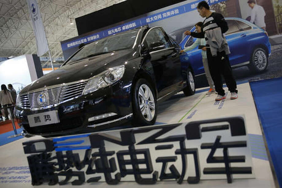 FILE - In this April26, 2016 file photo, visitors examine a Chinese automaker Denza electric vehicle on display at the Beijing International Automotive Exhibition in Beijing. China's auto sales growth accelerated in July, an industry group said Friday, Aug. 12, while General Motors Co. and Ford Motor Co. reported record demand for the month. Sales in the world's biggest auto market rose 26.3 percent to 1.6 million units, the China Association of Automobile Manufacturers said. (AP Photo/Andy Wong, File) Photo: Andy Wong