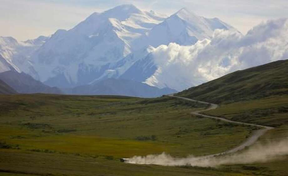 FILE - In this Aug. 8, 2013, file photo, a tour bus kicks up dust during a sunny day at Denali National Park in Alaska as Mount Denali appears in the background. Activists protested outside a state office building in Fairbanks, Alaska, on Aug.10, 2016, to demand Alaska Gov. Bill Walker to end wolf hunting near the park in light of its declining wolf population (AP Photo/Manuel Valdes, File) Photo: Manuel Valdes