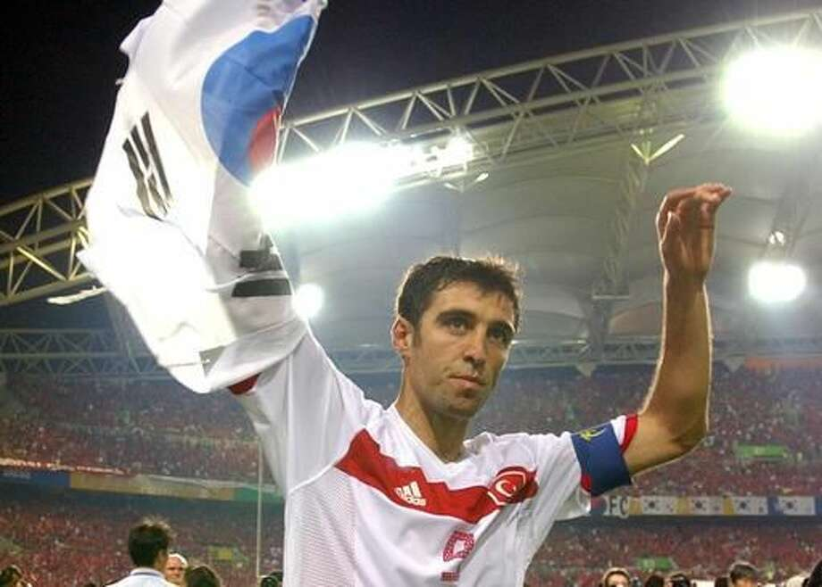 FILE - In this Saturday, June 29, 2002, file photo, Turkey's Hakan Sukur holds a South Korean flag at the end of the 2002 World Cup third place playoff soccer match between South Korea and Turkey, at the Daegu World Cup stadium, in Daegu, South Korea. Turkey's state-run news agency reports Friday, Aug. 12, 2016, authorities have issued an arrest warrant for former soccer star and legislator Hakan Sukur over his alleged links to a U.S.-based Muslim cleric, accused by Turkey of masterminding last month's failed coup. (AP Photo/Vincent Yu, FILE) Photo: Vincent Yu, Associated Press