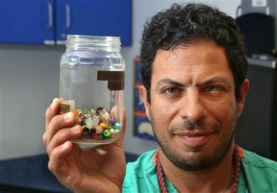 Charles Elmaraghy MD, Chief of the Ear, Nose and Throat Services at Nationwide Children's Hospital holds a collection of what children stuck in their ear, or up their nose on July 6, 2016 in Columbus, Ohio. From just the past couple of months, the jar contains dozens of beads, coins, pebbles and jewels. (Tom Dodge /The Columbus Dispatch via AP) Photo: Tom Dodge