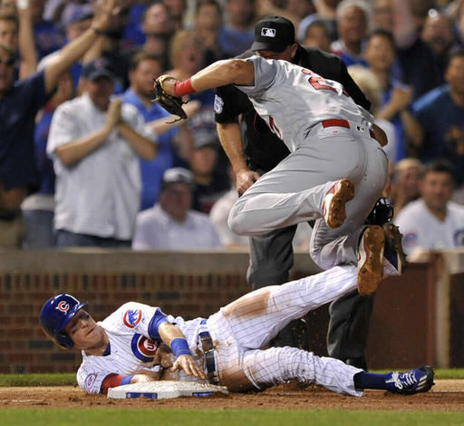 Chicago Cubs' Chris Coghlan slides safely at third base on a David Ross double while St. Louis Cardinals third baseman misses the tag during the fifth inning of a baseball game Thursday, Aug. 11, 2016, in Chicago. (AP Photo/Paul Beaty) Photo: Paul Beaty