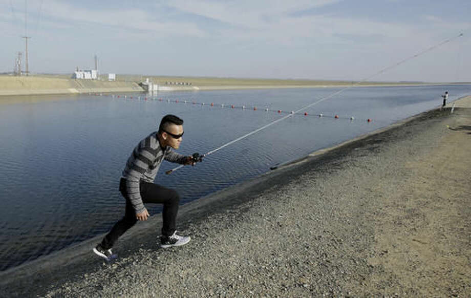 FILE- In this Feb. 25, 2016, file photo, Sha Xinog, climbs the bank to get more bait while fishing along the California Aquaduct near Firebaugh, Calif. Critics and a California lawmaker want more answers from Gov. Jerry Brown's administration on who's paying for a proposed giant water project. That's after a Southern California water district said Thursday, Aug. 11, 2016, that Brown's administration is now stating that state or federal funds will be used to finish planning for two $16 billion water tunnels. (AP Photo/Rich Pedroncelli, File) Photo: Rich Pedroncelli