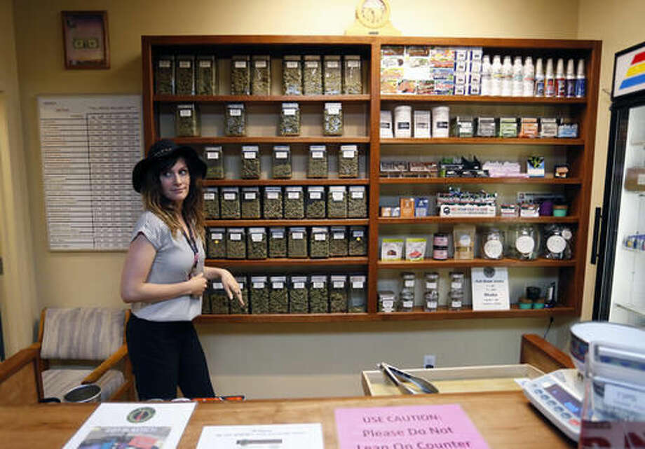 Assistant manager Jaclyn Stafford works behind the sales counter at The Station, a retail and medical cannabis dispensary, in Boulder, Colo., Thursday, Aug. 11, 2016. The DEA announced Thursday, Aug. 11, 2016 that the Obama administration will keep marijuana on the list of the most dangerous drugs, despite growing popular support for legalization, but will allow more research into its possible medical benefits. (AP Photo/Brennan Linsley) Photo: Brennan Linsley