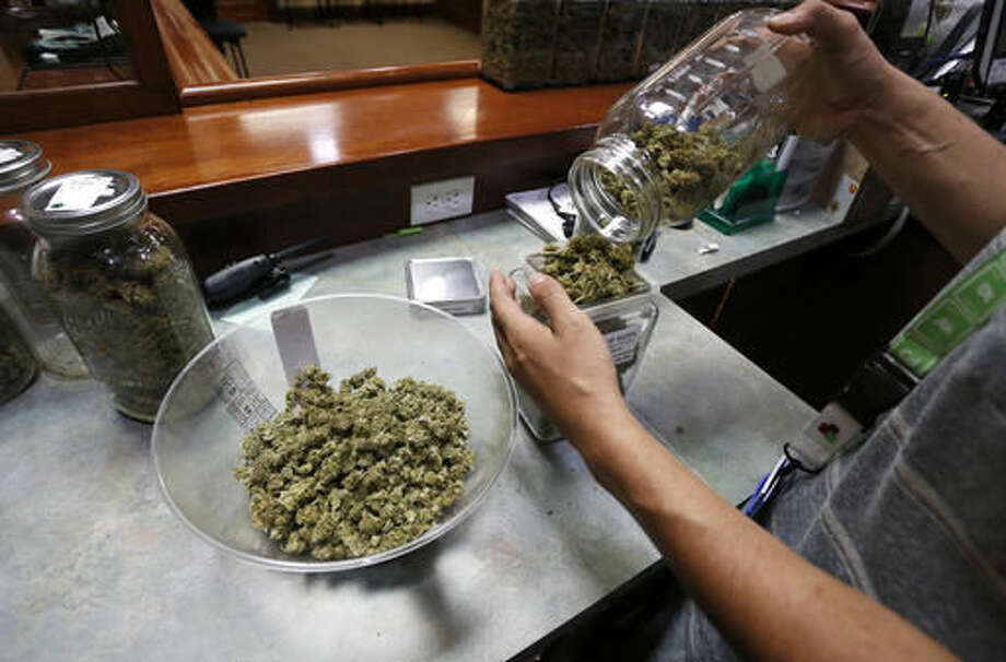 An employee places marijuana for sale into glass containers at The Station, a retail and medical cannabis dispensary, in Boulder, Colo., Thursday, Aug. 11, 2016. The DEA announced Thursday, Aug. 11, 2016 that the Obama administration will keep marijuana on the list of the most dangerous drugs, despite growing popular support for legalization, but will allow more research into its possible medical benefits. (AP Photo/Brennan Linsley) Photo: Brennan Linsley