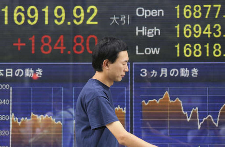 A man walks by an electronic stock board of a securities firm in Tokyo showing Japan's Nikkei 225 stock index that rose 184.80 points or 1.10 percent to close at 16,919.92, Friday, Aug. 12, 2016. Asian shares rose Friday, tracking the rally in U.S. stocks that was driven by strong gains by energy companies and retailers. Rising oil prices also lifted sentiment. The retailers' earnings fueled optimism for the U.S. government's latest monthly tally of retail sales Friday. (AP Photo/Koji Sasahara) Photo: Koji Sasahara