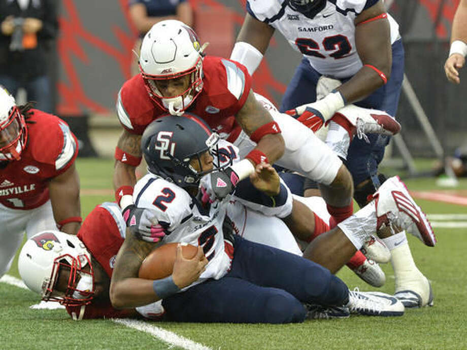 FILE - In this Sept. 26, 2015, file photo, Samford quarterback Michael Eubank (2) is sacked by Louisville nose tackle Deangelo Brown, bottom, and cornerback Jaire Alexander during the first half of their NCAA college football game, in Louisville, Ky. (AP Photo/Timothy D. Easley, File) Photo: Timothy D. Easley