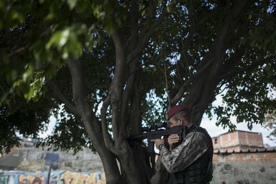 A Brazil's national security force officer takes position during a police operation in search for criminals in Vila do Joao, part of the Mare complex of slums during the 2016 Summer Olympics in Rio de Janeiro, Brazil, Thursday, Aug. 11, 2016. A police officer has died after being shot in the head when he and two others working security at the Rio Olympics got lost near a slum and encountered gunfire. (AP Photo/Felipe Dana) Photo: Felipe Dana